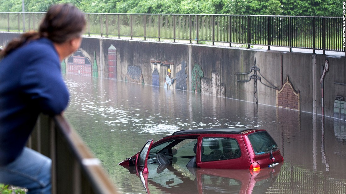 A man looks at a flooded car on a street in Oberhausen, Germany, after a heavy storm on Monday, May 30.
