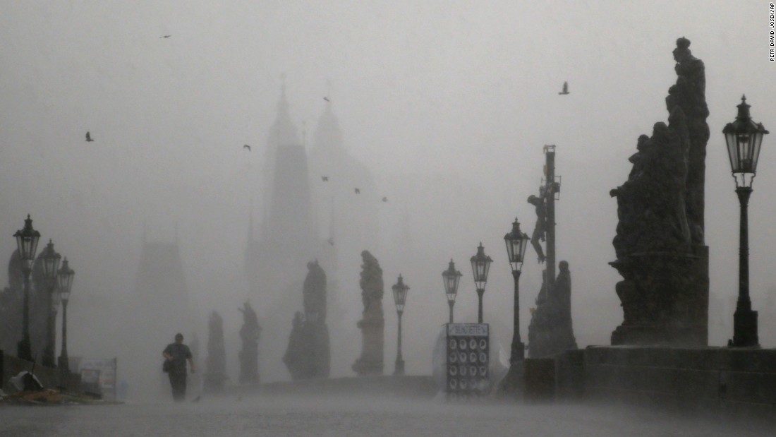 A man crosses the Charles Bridge during a storm in Prague, Czech Republic, on Tuesday, May 31.