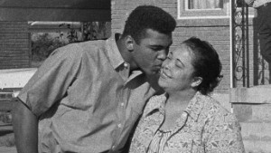 Cassius Clay kisses his mother, Odessa, in front of their Louisville, Kentucky home as his father, Cassius Sr., and brother, Rudy, look on 1963 © 1978 Gunther