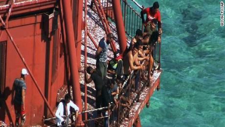 In this Friday, May 20, 2016 image made from video a group of Cubans stand atop American Shoal Lighthouse off Sugarloaf Key in a standoff with Coast Guard, in the Florida Keys. The group of migrants who fled Cuba in a homemade boat and climbed onto the 136-year-old lighthouse off the Florida Keys should be allowed to stay in the U.S., according to a federal lawsuit filed on their behalf.