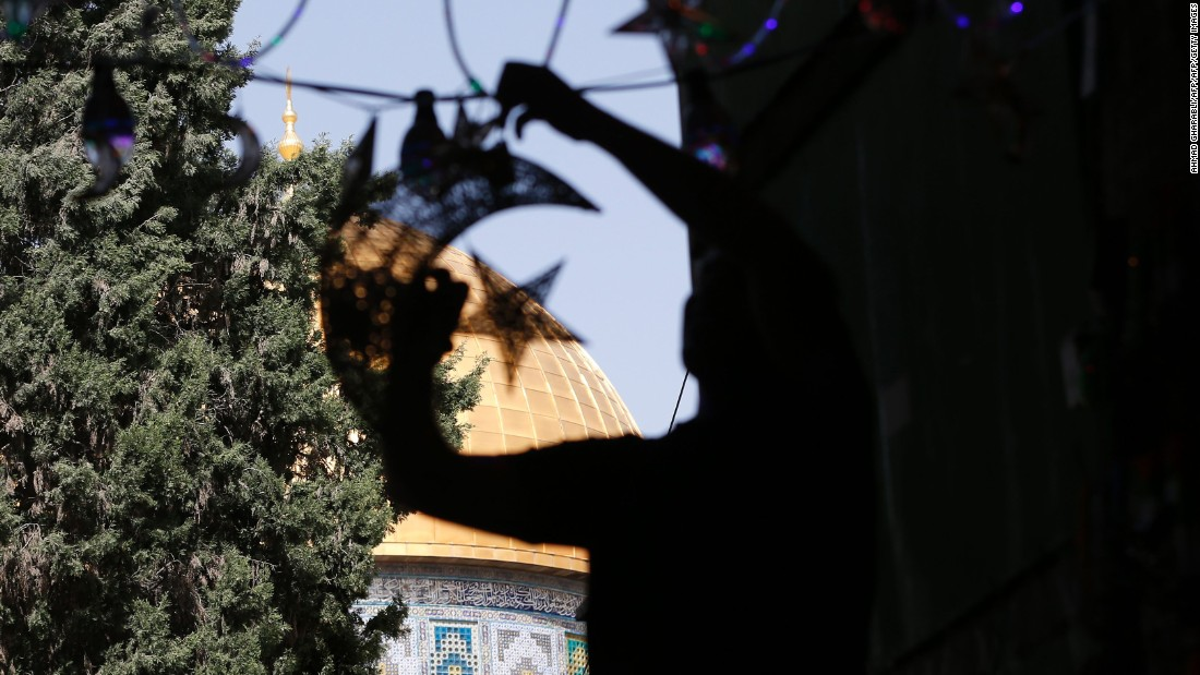 A Palestinian man decorates his shop with lights near the entrance of the al-Aqsa mosque in Jerusalem on June 5.