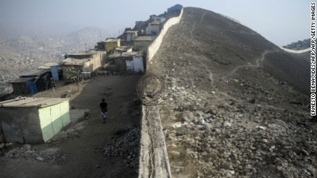 """Picture of the so-called """"Wall of Shame"""" in the outskirts of Lima on April 08, 2016.  The place began to be populated 20 years ago, with migration of Andean people displaced by poverty and violence of the guerrillas from the countryside to the city. The 10km length wall separates dusty huts without electricity or water from mansions with pool and green areas, recalling that economic growth is not for everyone. / AFP / ERNESTO BENAVIDES        (Photo credit should read ERNESTO BENAVIDES/AFP/Getty Images)"""