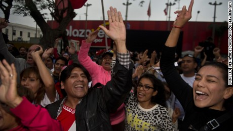 """Supporters of Peruvian presidential candidate Pedro Pablo Kuczynski celebrate the preliminary results, pointing to a photo finish, at the """"Peruanos por el Kambio"""" party headquarters in Lima on June 5, 2016.  Peruvians voted Sunday in a close-fought runoff election that will decide whether Kuczynski or Keiko Fujimori, the daughter of former president Alberto Fujimori, in jail for corruption and crimes against humanity, will be their new leader. / AFP / ERNESTO BENAVIDES        (Photo credit should read ERNESTO BENAVIDES/AFP/Getty Images)"""