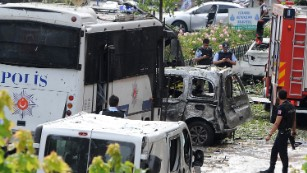 Police officers inspect the site of Tuesday's attack that targeted a police bus.