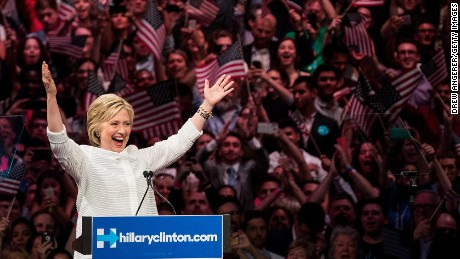 Democratic presidential candidate Hillary Clinton gestures to the crowd at the start of her remarks during a primary night rally at the Duggal Greenhouse in the Brooklyn Navy Yard, June 7, 2016 in the Brooklyn borough of New York City. Clinton  has secured enough delegates and commitments from superdelegates to become the Democratic Party's presumptive presidential nominee. She will become the first woman in U.S. history to secure the presidential nomination of one of the country's two major political parties.