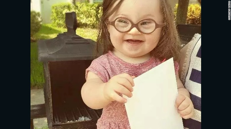 Emersyn Baker, 15 months old, holds a letter her mom wrote and sent to their doctor.