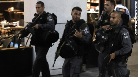 Israeli security forces walk at a shopping complex in the Mediterranean coastal city of Tel Aviv following a shooting attack on June 8, 2016. At least three people were killed and several wounded in the shooting spree, emergency services said. Police said that it appeared to be a militant attack, but they could not immediately give any details of the attacker or victims.