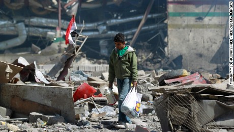 TOPSHOT - A Yemeni boy walks amid the ruins of a school and a bowling club hit by an air-strike carried out by the Saudi-led coalition, in the capital Sanaa, on February 12, 2016.   / AFP / MOHAMMED HUWAIS        (Photo credit should read MOHAMMED HUWAIS/AFP/Getty Images)