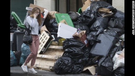 "A woman walks past a pile of un-collected rubbish on June 10, 2016 in Paris.  Paris Mayor Anne Hidalgo promised on June 10, 2016 that ""all rubbish"" piling up in the city due to an ongoing strike would be collected, as fans arrive for the Euro 2016 football championships."