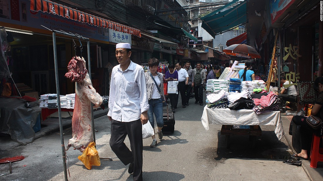 After slaughtering this lamb on street, the Uygur restaurateurs from north-west China hang the meat ready to cook for customers.