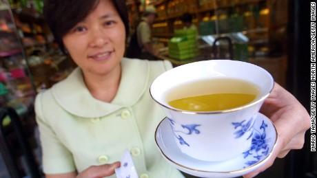 392086 01: Susan Zhu dsiplays a cup of green tea July 18, 2001 at Ten Ren and Ginseng Co., a store in New York City''s Chinatown. A study released July 18, 2001 shows that green tea may reduce the risks of breast cancer. (Photo by Mario Tama/Getty Images)