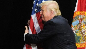 TAMPA, FLORIDA - JUNE 11:  Republican presidential candidate Donald Trump embraces the United States flag during a campaign rally  at the Tampa Convention Center on June 11, 2016 in Tampa, Florida. Florida Gov. Rick Scott spoke at the rally and introduced Trump. (Photo by Gerardo Mora/Getty Images)