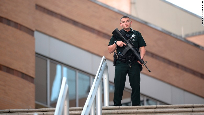 A police officer stands guard outside an Orlando hospital after the mass shooting.