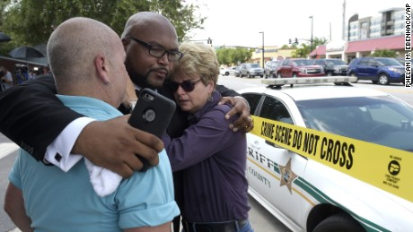 Terry DeCarlo, executive director of the LGBT Center of Central Florida, left, Kelvin Cobaris, pastor of The Impact Church, center, and Orlando City Commissioner Patty Sheehan console each other after the shooting at the Pulse nightclub in Orlando, Florida, Sunday, June 12.