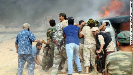 Forces loyal to Libya's UN-backed unity government attempt to evacuate a passenger stuck inside a vehicle after it caught on fire following a car-bomb attack nearby carried out by an Islamic State (IS) group jihadist at the western entrance of Sirte on June 2, 2016. According to Libyan officials fighting resumed on June 1 on the outskirts of Sirte between their forces and jihadist during which three pro-government troops had been killed and 10 more wounded. Sirte was the hometown of slain dictator Moamer Kadhafi and, since seizing it in June last year, IS has turned it into a recruitment and training camp / AFP / MAHMUD TURKIA        (Photo credit should read MAHMUD TURKIA/AFP/Getty Images)