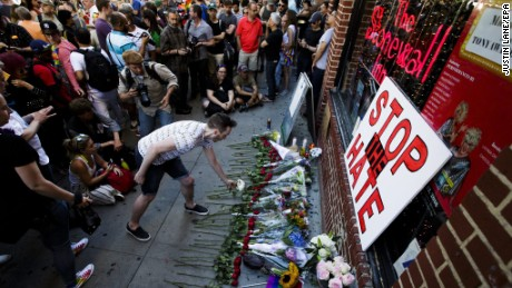 People gather for a vigil for the victims of the mass shooting at an Orlando, Florida gay club outside of the Stonewall Inn, in New York, on Sunday, June 12.