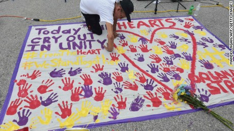 """A man places a hand print on a makeshift memorial in a parking lot near the Pulse nightclub in Orlando, Florida on June 12, 2016.A somber President Barack Obama  expressed grief and outrage at the """"horrific massacre"""" of 50 late-night revelers at an Orlando gay club, branding it an act of terror and hate. / AFP PHOTO / Mandel NGANMANDEL NGAN/AFP/Getty Images"""