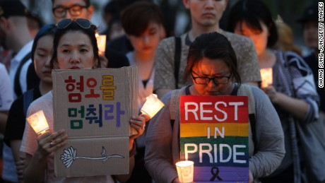People gather during a vigil in downtown Seoul to remember victims of the shooting at an Orlando nightclub on June 13, 2016 in Seoul, South Korea. An American-born man who had recently pledged allegiance to ISIS killed 50 people early morning on June 12, 2016 at a gay nightclub in Orlando, Florida. The massacre was the deadliest mass shooting in the United States.