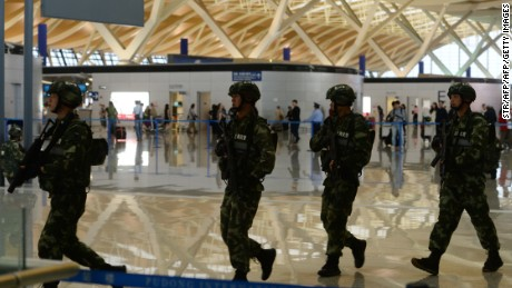 """Paramilitary police officers patrol inside Pudong airport in Shanghai after an explosion near a check-in counter on June 12, 2016.  A blast caused by """"home-made"""" explosives injured four people and sparked a major security alert at the main international airport in China's commercial hub of Shanghai on June 12, according to the operator and state media. / AFP / STR / China OUT        (Photo credit should read STR/AFP/Getty Images)"""