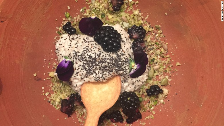 Menu items, like this dessert of blackberries, coconut and chia mouse with raw crumble, are served in earthenware dishes and eaten with edible cutlery.