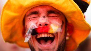 A German soccer fan celebrates prior to the Euro 2016 Group C soccer match between Germany and Ukraine in the soccer fan zone near the Brandenburg Gate, in Berlin, Sunday, June 12, 2016. (AP Photo/Markus Schreiber)