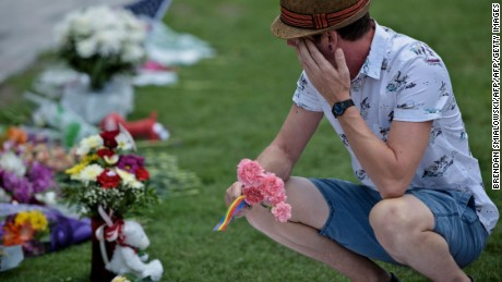 Jonathan Dalton who lost friends visits a makeshift memorial outside the Dr. Phillips Center for the Performing Arts for the mass shooting victims at the Pulse nightclub June 13, 2016 in Orlando, Florida. The American gunman who launched a murderous assault on a gay nightclub in Orlando was radicalized by Islamist propaganda, officials said Monday, as they grappled with the worst terror attack on US soil since 9/11.   / AFP / Brendan Smialowski        (Photo credit should read BRENDAN SMIALOWSKI/AFP/Getty Images)