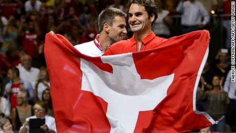 Switzerland's Roger Federer (R) waves his national flag next to teammate Michael Lammer as they celebrate winning the Davis Cup semi-final between Switzerland and Italy on September 14, 2014 in Geneva. AFP PHOTO / FABRICE COFFRINI        (Photo credit should read FABRICE COFFRINI/AFP/Getty Images)