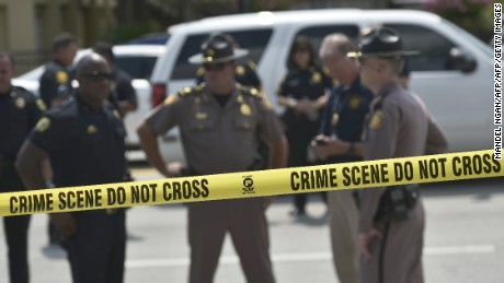 Police stand behind a crime scene tape near the mass shooting at the Pulse nightclub on  in Orlando, Florida on June 12, 2016.