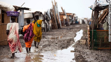 Women carry their belongings inside the Protection of Civilians (PoC) site in Malakal, on June 14, 2016. The rainy season started and made the living conditions very difficult for the displaced people in one of the most crowded PoC in South Sudan. In some areas, the density in this camp is around 9 square meters per person, which is highly below the UN standards (30). People are facing health risks such malaria and cholera due to the lack of good draining infrastructures. 32,000 people are currently living in this PoC that faced one of the most violent episodes in the South Sudanese civil war.