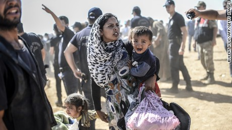 A Syrian Kurdish woman crosses the border between Syria and Turkey at the southeastern town of Suruc in Sanliurfa province on September 23, 2014. The UN refugee agency warned Tuesday that as many as 400,000 people may flee to Turkey from Syria's Kurdish region to escape attacks by the Islamic State group.