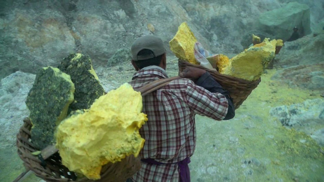 Miners load the sulfur ore into pairs of baskets at opposite ends of a long bar of wood.