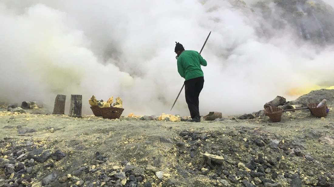 Indonesian men use long metal poles to break off chunks of yellow crust -- sulfur -- from the crater floor.
