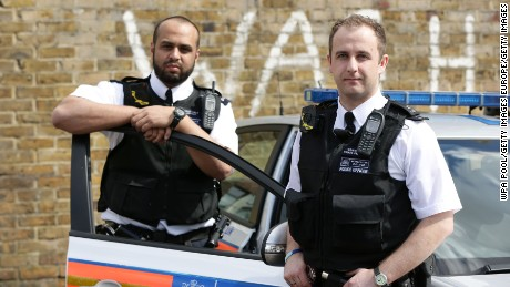 LONDON - MAY 6:  Constable Yasa Amerat (left) and Constable Craig Pearson wearing their body-worn video (BWV) cameras, ahead of a year-long pilot scheme by the Metropolitan police, at Kentish Town on May 6, 2014 in London, England. Officers with the Metropolitan Police will be begin wearing tiny cameras on their uniform, designed to capture evidence at scenes of crime and help support prosecution cases. The trial, thought to be the largest in the world, will see a total of 500 cameras distributed to 10 London boroughs. (Photo by Yui Mok - WPA Pool/Getty Images)