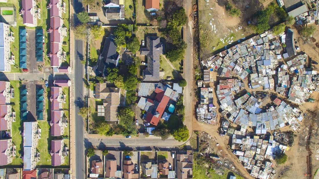 """When Miller tried to access Cape Town's more affluent areas, he was stopped by security guards. """"You have two or three meter high fences with electric fencing and often barbed wire, which is the norm for South Africa"""", he says. His drone shots allowed him to bypass security."""