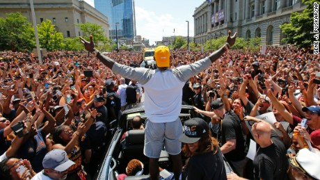 Cleveland Cavaliers' LeBron James, center, stands in the back of a Rolls Royce as it makes its way through the crowd lining the parade route in downtown Cleveland, Wednesday, June 22, 2016, celebrating the basketball team's NBA championship. (AP Photo/Gene J. Puskar)