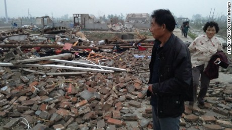 Residents look through the rubble of destroyed houses after a tornado hit Yancheng, Jiangsu province on June 23, 2016.