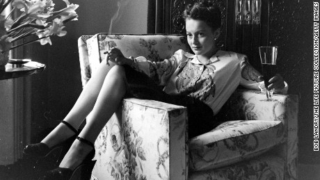 Actress Olivia De Havilland holding lit cigarette as she holds a glass of beer in the other while relaxing at home.  (Photo by Bob Landry/The LIFE Picture Collection/Getty Images)