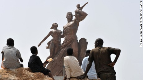 "Children look at the ""African Renaissance Monument"" (up) on April 1, 2010 in Dakar during preparations for the April 3 inauguration where heads of states are expected. The controversial bronze work -- which at 50 metres (164 feet) stands four metres taller than the Statue of Liberty -- depicts a couple rising from the mouth of a volcano. To finance the project, the state has been selling off government land to the private sector, a policy that has itself been criticised.  AFP/PHOTO SEYLLOU        (Photo credit should read SEYLLOU DIALLO/AFP/Getty Images)"