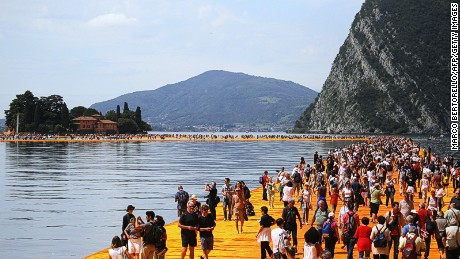 An installation entitled 'The Floating Piers' created by artist Christo Vladimirov Javacheff on Iseo Lake, in northern Italy, on June 18, 2016. Some 200,000 floating cubes create a 3-kilometers runway connecting the village of Sulzano to the small island of Monte Isola on the Iseo Lake for a 16-day outdoor installation opening today. / AFP / MARCO BERTORELLO / RESTRICTED TO EDITORIAL USE - MANDATORY MENTION OF THE ARTIST UPON PUBLICATION - TO ILLUSTRATE THE EVENT AS SPECIFIED IN THE CAPTION (Photo credit should read MARCO BERTORELLO/AFP/Getty Images)