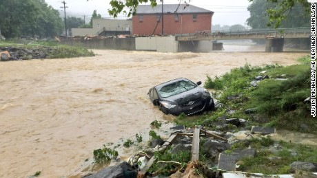 A vehicle rests on the in a stream after a heavy rain near White Sulphur Springs, W.Va., Friday, June 24, 2016. Multiple fatalities have been reported in flooding that has devastated parts of the state, a state official said Friday morning.