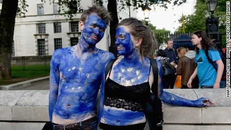 LONDON, ENGLAND- JUNE 24: A young couple painted as EU flags protest on outside Downing Street against the United Kingdom's decision to leave the EU following the referendum on June 24, 2016 in London, United Kingdom. The United Kingdom has gone to the polls to decide whether or not the country wishes to remain within the European Union. After a hard fought campaign from both REMAIN and LEAVE the vote is too close to call. A result on the referendum is expected on Friday morning.  (Photo by Mary Turner/Getty Images)