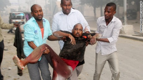Somali men help a wounded civilian who was wounded in a suicide car bomb attack on a hotel in Mogadishu, Somalia, Saturday, June 25, 2016. A Somali police officer says a suicide car bomber detonated an explosives-laden vehicle at the gate of a hotel in Mogadishu followed by gunmen who were fighting their way into the hotel.(AP Photo/Farah Abdi Warsameh)