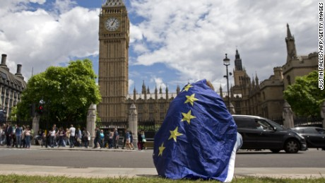 A demonstrator draped in an EU flag sits on floor during a protest against the outcome of the UK's June 23 referendum on the European Union in central London on June 25, 2016.