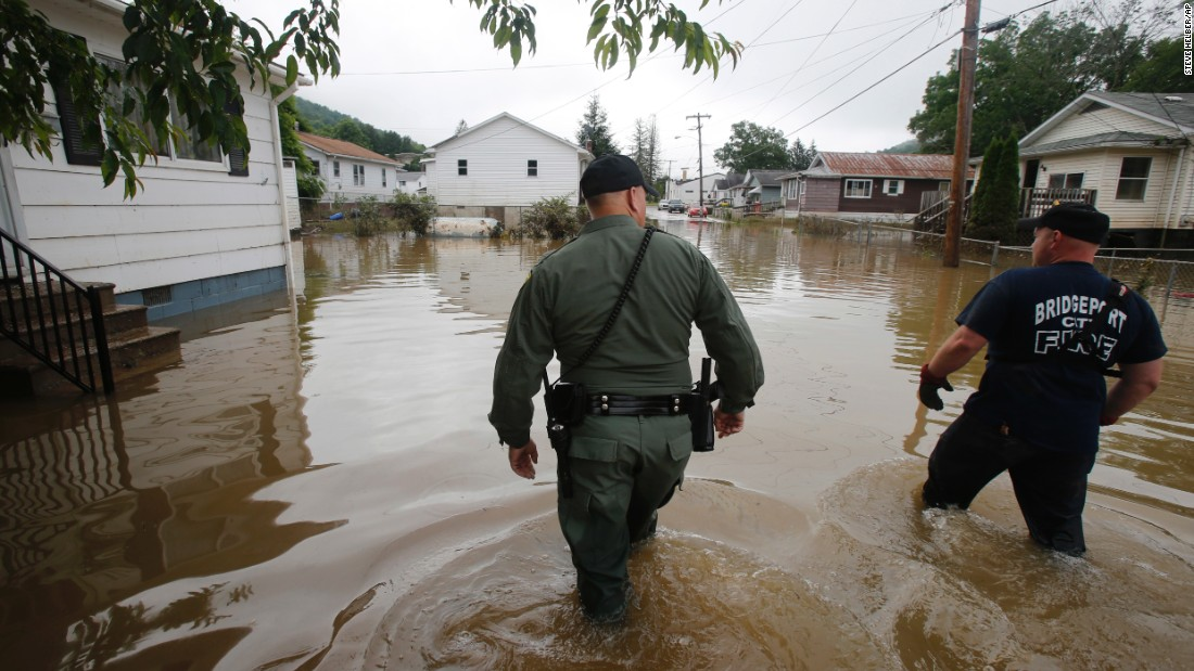 West Virginia State Trooper C.S. Hartman, left, and Bridgeport firefighter Ryan Moran wade through flooded streets as they search homes in Rainelle, West Virginia, on June 25.