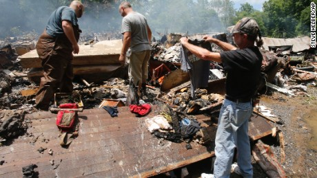 Ron Scott, right, recovers a shirt from the burned remnants of his home that was swept off it's foundation and burned after from severe flooding hit in White Sulphur Springs, W. Va., Friday, June 24, 2016. A deluge of 9 inches of rain on parts of West Virginia destroyed or damaged more than 100 homes and knocked out power to tens of thousands of homes and businesses. (AP Photo/Steve Helber