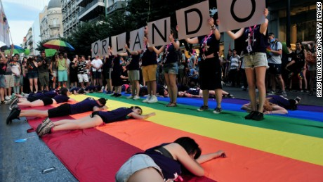 """People holds placards reading """"Orlando"""" in memory of the victims of Orlando's gay bar shooting as thousands of people parade in the streets of Thessaloniki, northern Greece."""