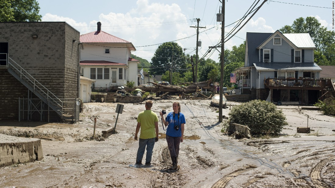 """People survey a mud-covered street after the floodwaters of the Elk River receded in Clendenin, West Virginia, on Saturday, June 25. <a href=""""http://www.cnn.com/2016/06/24/us/gallery/west-virginia-flooding/index.html"""" target=""""_blank"""">Fast-moving floodwaters</a> killed at least 24 people in the state."""