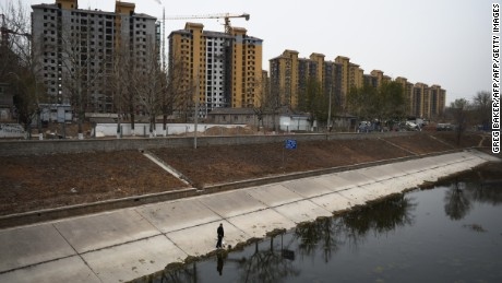 A man fishes near rows of newly built apartments in Beijing on November 27, 2014. China's economy has been slammed by a deflating property bubble and weak export growth, as well as a government crackdown on corruption. AFP PHOTO/Greg BAKER        (Photo credit should read GREG BAKER/AFP/Getty Images)