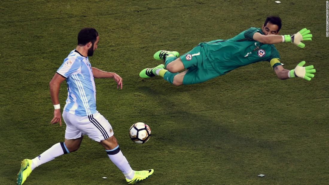 Argentina's Gonzalo Higuain, left,  prepares to shoot against Chile's goalie Claudio Bravo.