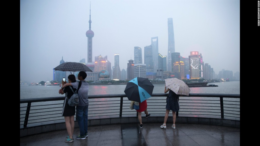 Tourists in Shanghai, China, stand along the promenade at the Bund on Friday, June 17.